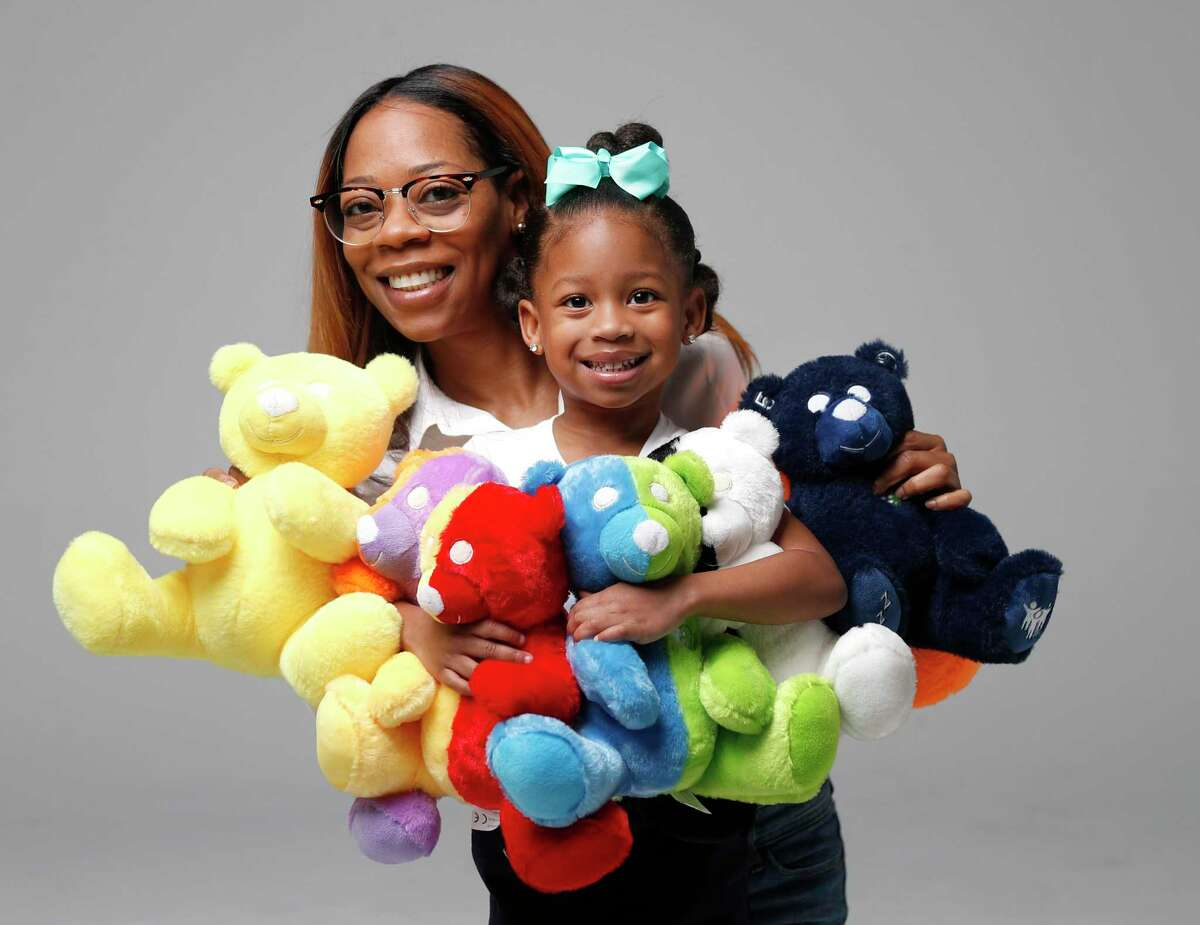 Tameka Maiden, and her daughter, Tori Thomas, 4, display the Cubby Love Bears line of educational toys that includes the dark-blue U'Neek - the Gifted Bear, designed for nonverbal kids with autism.