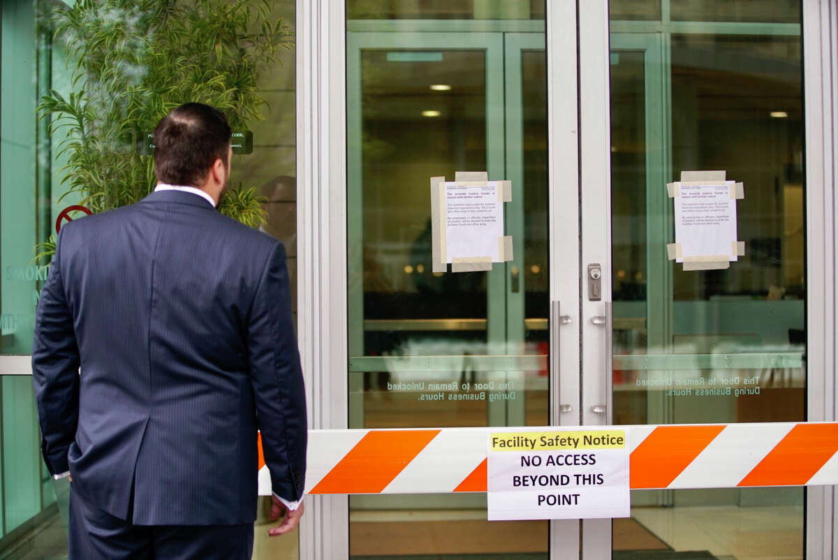 The doors are blocked and signs are up on the doors of the Harris County Juvenile Justice Center Friday, March 13, 2020, in downtown Houston.