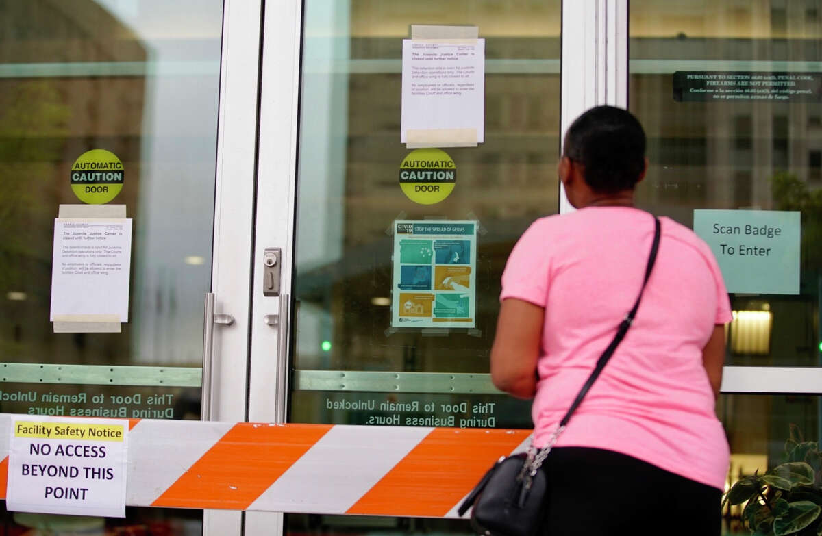 Aurelia Ray, of Houston, looks at the locked doors that are blocked and signs posted on the doors of the Harris County Juvenile Justice Center Friday, March 13, 2020, in downtown Houston. Ray has a daughter currently locked in the building who she is trying to get an inhaler to.