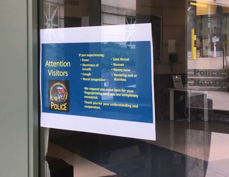 A sign on the door at the Greenwich Police Department asks visitors who are ill to return when they are recovered. Photo: / Robert Marchant / Hearst Connecticut Media