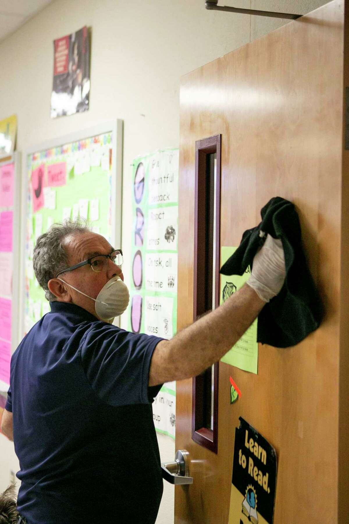 Oscar Marin cleans a classroom door to remove any possibility of the coronavirus on surfaces at Dolph Briscoe Middle School in San Antonio on March 9, 2020.