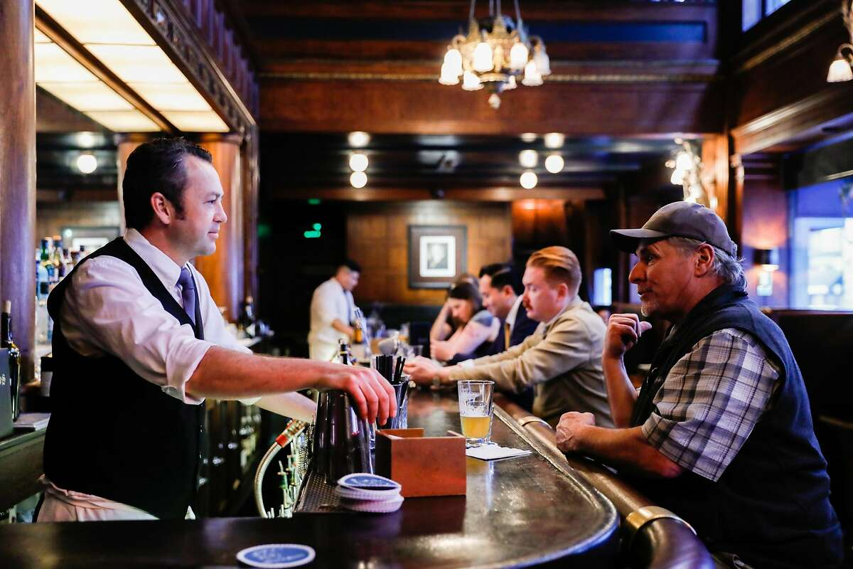 Bartender Shanty De Luca (left) chats with Paulie (right) at House of Shields on Wednesday, March 11, 2020 in San Francisco, California. The coronavirus has impacted many areas because people have been advised by their companies to work from home.