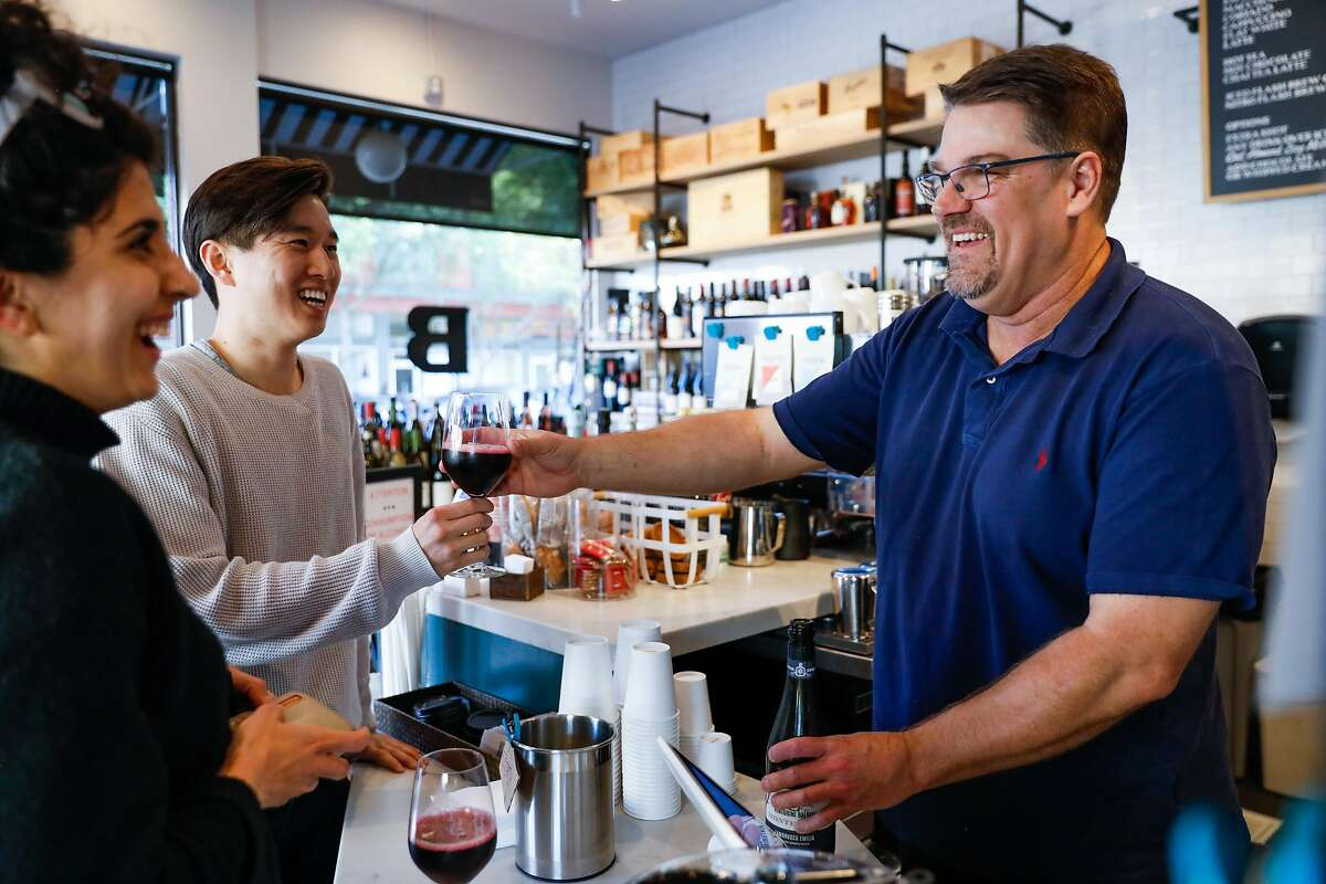 Will Eagle, owner of Breck�s on Clement Street gives a glass of wine to Jon Yoo (center) while laughing with Meena Rezaei (left) on Wednesday, March 11, 2020 in San Francisco, California. The coronavirus has impacted many areas because people have been advised by their companies to work from home.