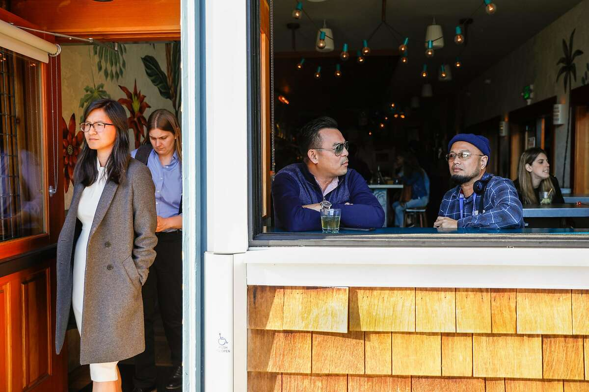 Fernando Aquino (center) and Russell Arayata (right) chat and have drinks at a bar on Hayes Street on Wednesday, March 11, 2020 in San Francisco, California. The coronavirus has impacted many areas because people have been advised by their companies to work from home.