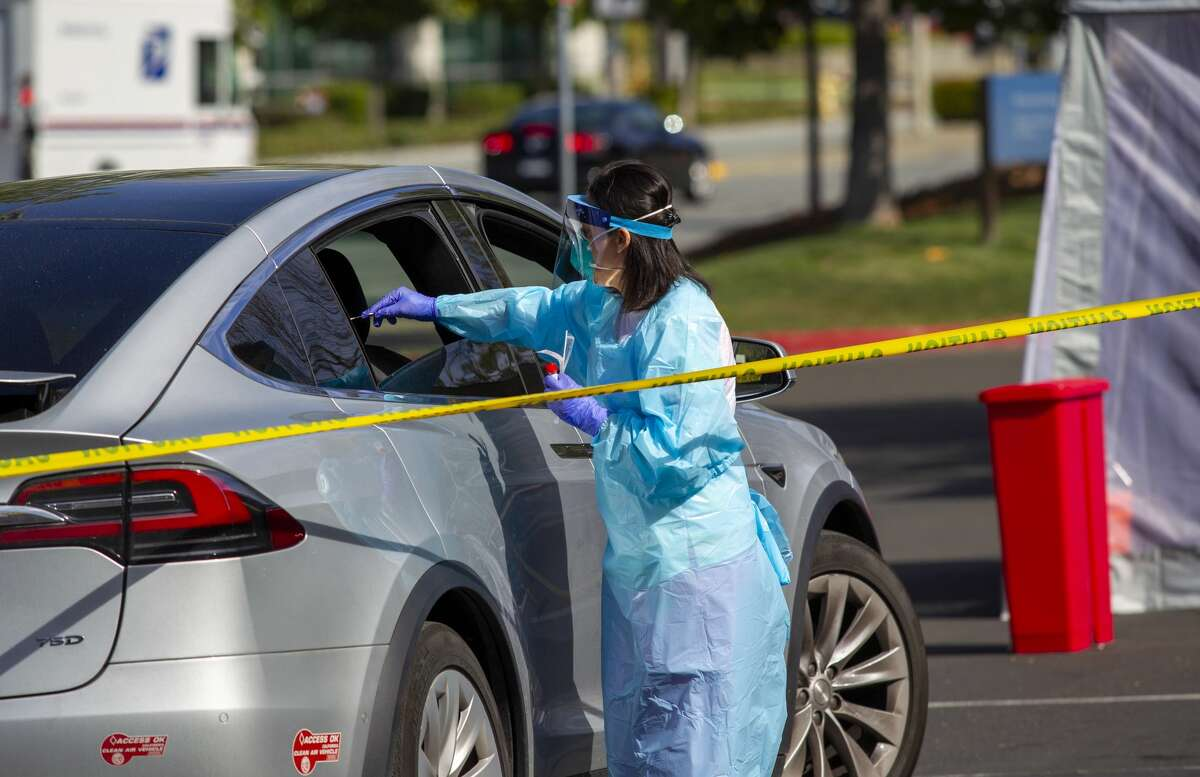 A Kaiser Permanente clinician swabs for COVID-19 while a patient sits in the car at one of Kaiser Permanente's drive-up testing sites in the Bay Area on March 11, 2020.