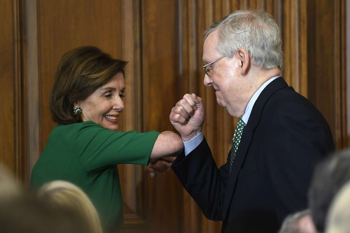 House Speaker Nancy Pelosi of Calif., left, and Senate Majority Leader Mitch McConnell of Ky., right, bump elbows as they attend a lunch with Irish Prime Minister Leo Varadkar on Capitol Hill in Washington, Thursday, March 12, 2020. (AP Photo/Susan Walsh)