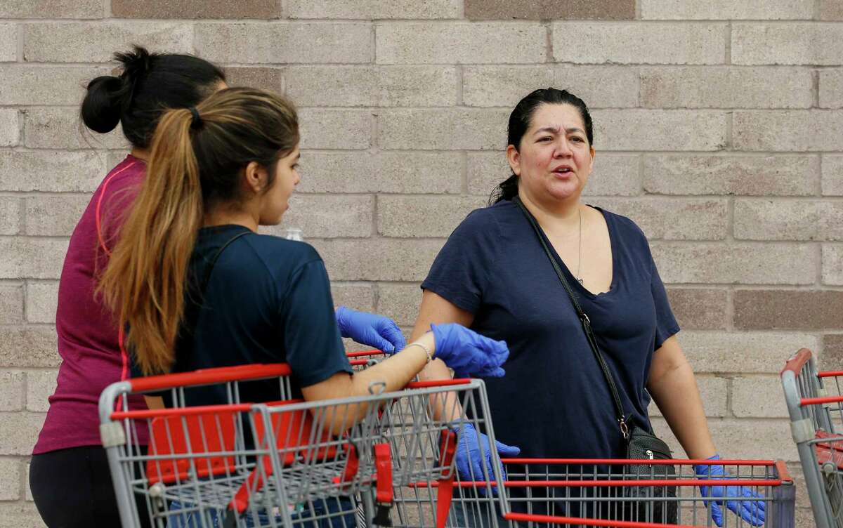 Women waiting in line for the Costco Wholesale at Bunker Hill Road to open wear gloves Friday, March 13, 2020, in Houston. People are rushing to grocery stores amid fears of the new coronavirus pandemic.