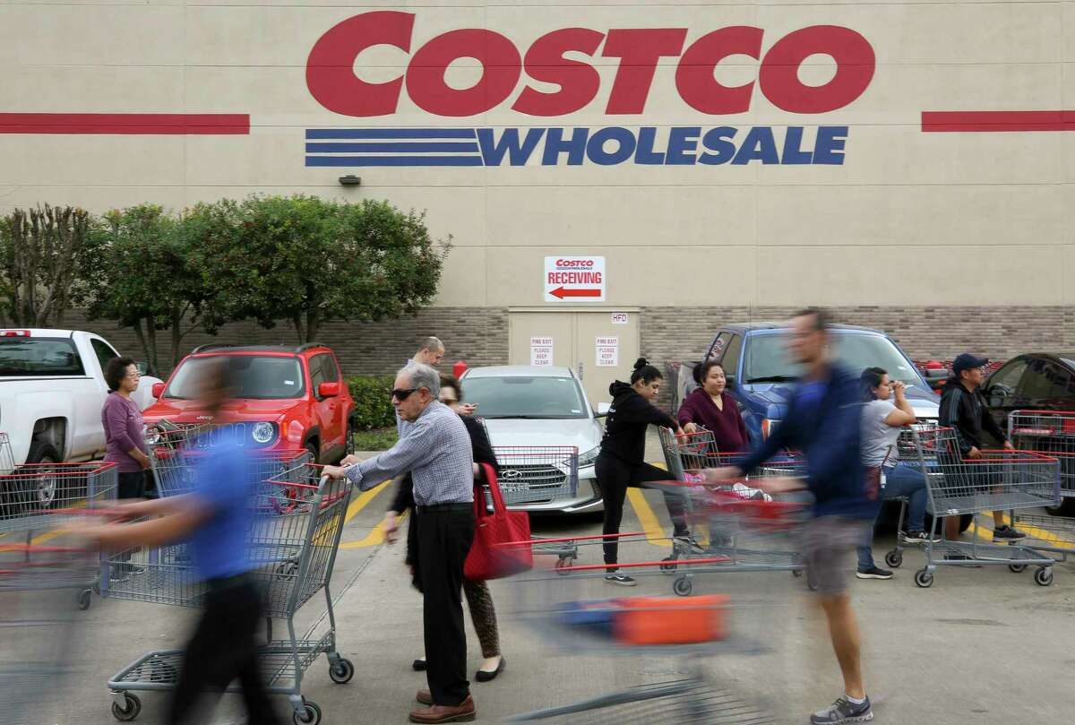 People wait in line for the Costco Wholesale at Bunker Hill Road to open Friday, March 13, 2020, in Houston. People are rushing to grocery stores amid fears of the new coronavirus pandemic.