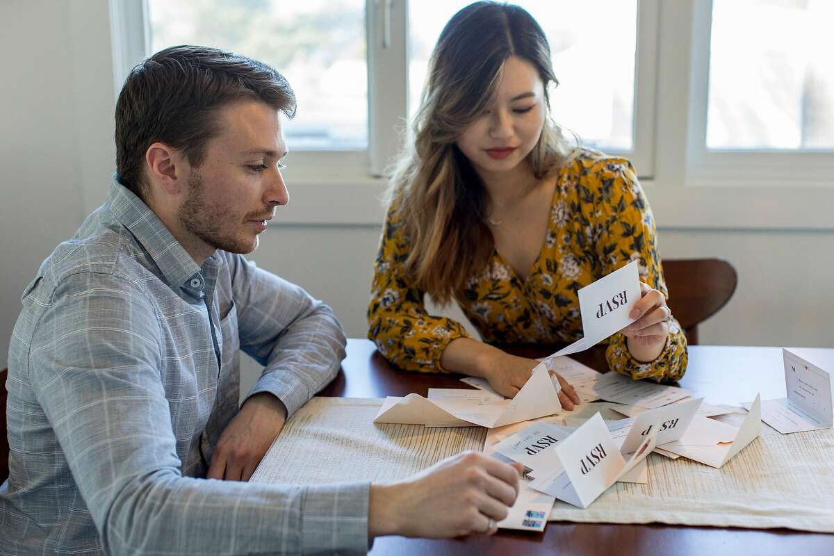 From left, James Hudon and Kristy Yeh look through RSVP cards for their wedding at their home in Montara, Calif. on Wednesday, March 11, 2020. were supposed to get married at the end of April, but they'll probably postpone the wedding because of the coronavirus. If they do, they could lose their $13,000 depositon the venue if they cancel.