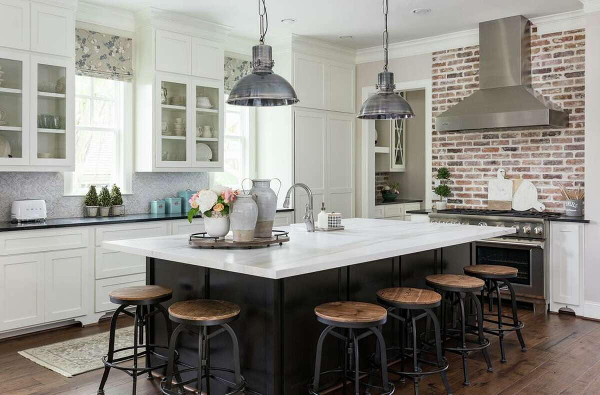 A large island that accommodates six barstools is a place where the Richards' can prepare food or eat a casual meal.