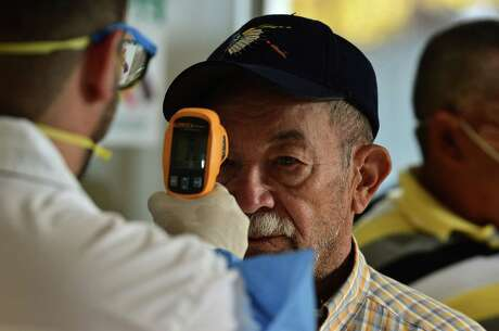 A doctor checks the temperature to a man at the Honduran Institute of Social Security (IHSS)  to discard symptoms of the new Coronavirus, COVID-19, in Tegucigalpa, on March 13, 2020. - The Honduran government has suspended classes at schools and universities. (Photo by ORLANDO SIERRA / AFP)