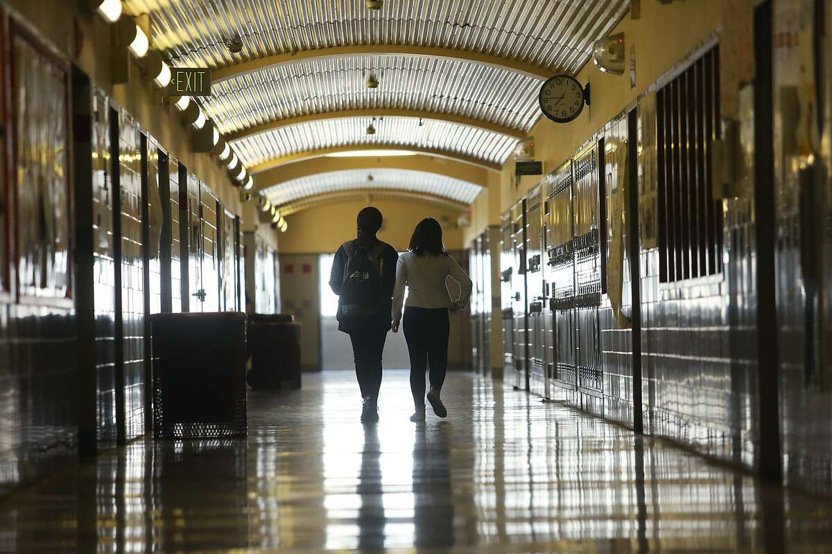 Two students walk through a corridor at Thurgood Marshall Academic High School on Thursday, March 12, 2020 in San Francisco, Calif.