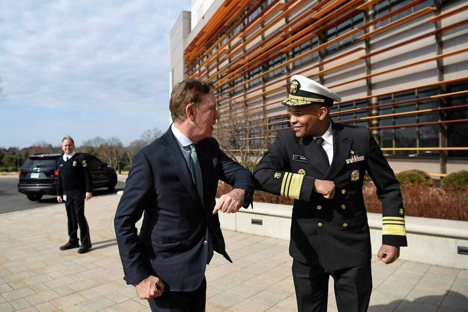U.S. Surgeon General Vice Admiral Jerome M. Adams, right, bumps elbows with Connecticut Gov. Ned Lamont as they meet for a visit the Connecticut State Public Health Laboratory, Monday, March 2, in Rocky Hill. The Surgeon General is encouraging people to bump elbows rather than shaking hands or fist bumps to help prevent the spread of COVID-19. Photo: Jessica Hill / Associated Press / Copyright 2020 The Associated Press. All rights reserved.