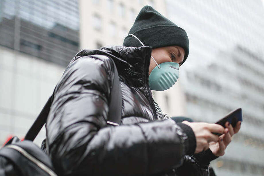 A pedestrian uses her phone while wearing a face mask. Photo: John Minchillo | AP