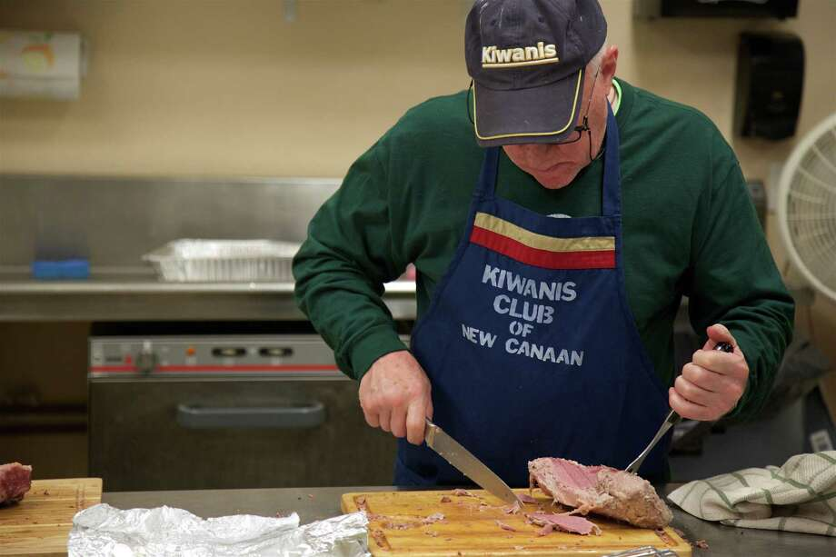 Volunteer Sperry DeCew of New Canaan carves the corned beef at a previous Kiwanis Club of New Canaan St. Patrick's Day Dinner and Social. Sunday's event was canceled because of COVID-19. Photo: Jarret Liotta / For Hearst Connecticut Media / Connecticut Post