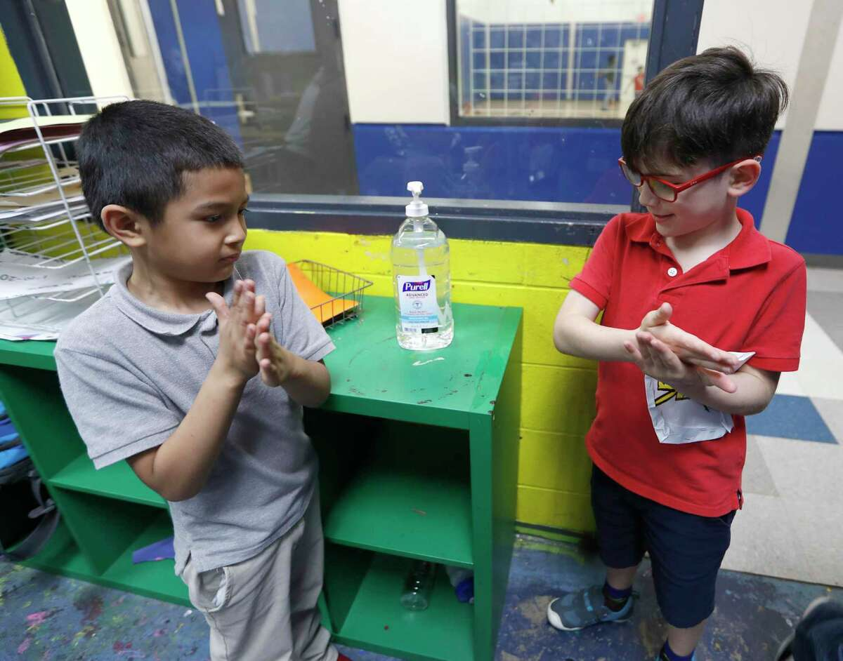 Victor Parache, 6, left, and Emiliano Arango, 7, use the hand sanitizer at the Heights Boys and Girls Club in Houston on Thursday. The club is helping to serve students in light of the novel coronavirus pandemic.