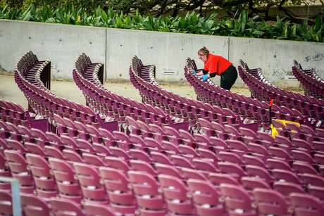 A worker cleans the seats at Miller Outdoor Theater, Friday, March 13, 2020, at Hermann Park in Houston.