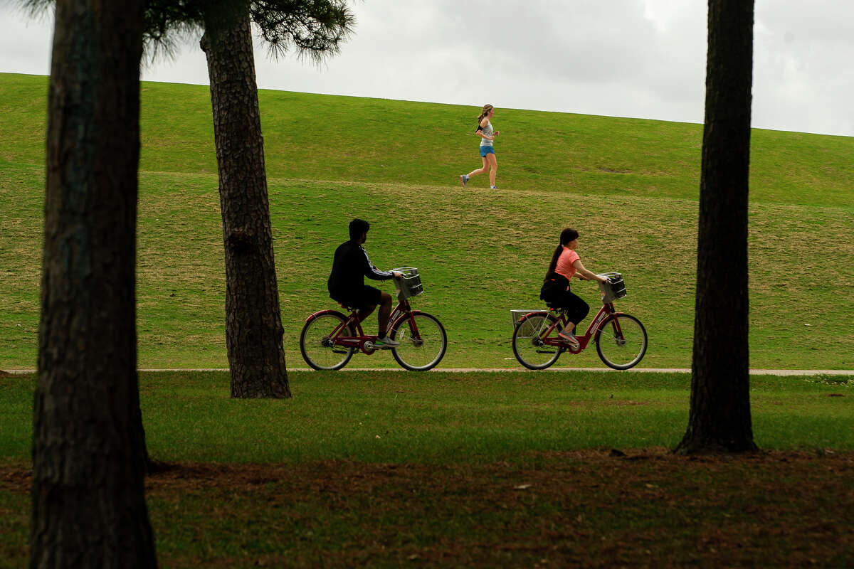 People enjoy the park, Friday, March 13, 2020, at Hermann Park in Houston.