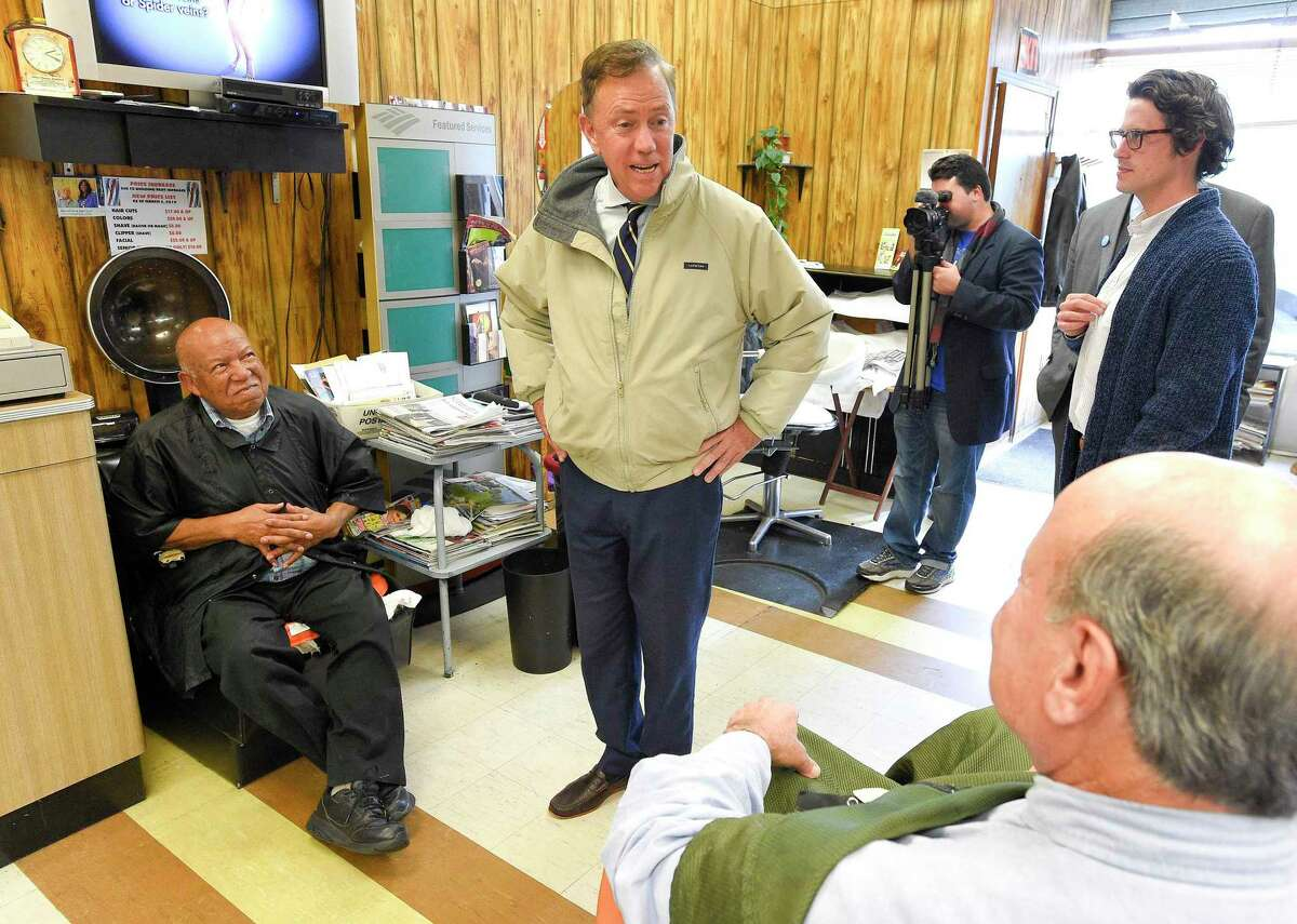 Democratic Governor candidate Ned Lamont, center, chats with barber/owner Thomas Bradford, at left, and Peter Muhlrad of Old Greenwich, at right, at Superior Barber and Beauty shop in Stamford, Connecticut., Tuesday, Oct. 16, 2018. Lamont was on a short city tour to share recently announced policy proposals on