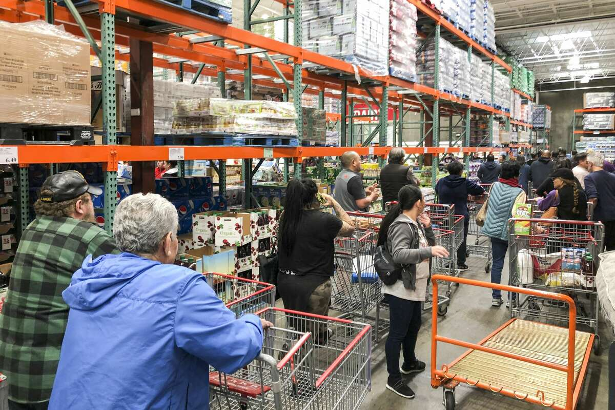 Shoppers in line for bottled water, toilet paper and paper towels at Costco in Vallejo, Friday, March 13, 2020.