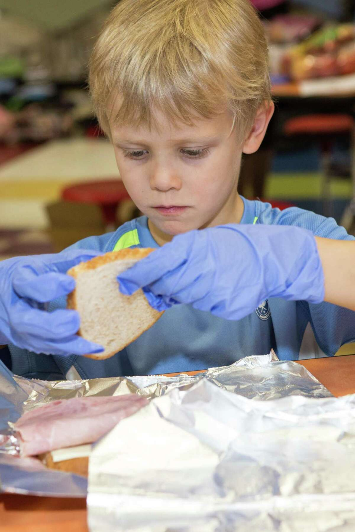 Kindergartener Hudson Schunkl is focused on the task of making a ham sandwich during a Stratfield School community-service project on May 1.