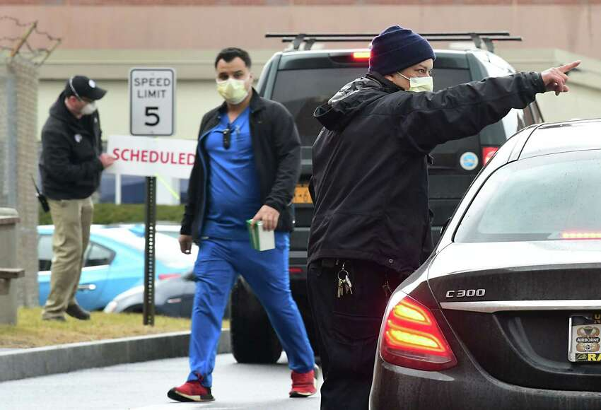 A hospital employee is seen directing cars as they drive up next to a tent set up in the rear parking lot of Albany Medical Center as a place to test people for COVID-19, also called the novel coronavirus on Friday, March 13, 2020 in Albany, N.Y. People in their cars are assessed according to their symptoms to whether they get tested for the virus. (Lori Van Buren/Times Union)