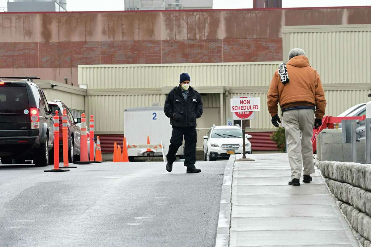 A hospital employee greets a person walking next to a tent set up in the rear parking lot of Albany Medical Center as a place to test people for COVID-19, also called the novel coronavirus on Friday, March 13, 2020 in Albany, N.Y. (Lori Van Buren/Times Union)