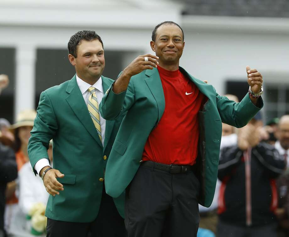 FILE - In this April 14, 2019, file photo, Patrick Reed, left, helps Tiger Woods with his green jacket after Woods won the Masters golf tournament, in Augusta, Ga. The annual rite of spring for golf won't happen this year. The Masters has been postponed until a later date. Augusta National did not indicate when the Masters would be played. That means there will be no golf at least for the next month. The Masters began in 1934 and only World War II has kept it from being played. This was the biggest shoe to drop for golf. The PGA Tour already canceled the next three events leading up to the Masters. Tiger Woods was to be going after his sixth green jacket. (AP Photo/Matt Slocum, File) Photo: Matt Slocum / Associated Press