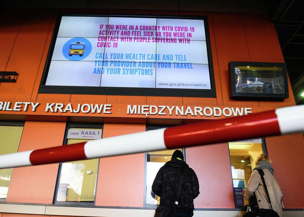 At a bus station in Krakow, Poland, an electronic sign urges travelers to alert their health care provider if they've been exposed to the coronavirus or are experiencing symptoms of COVID-19, the disease it causes.