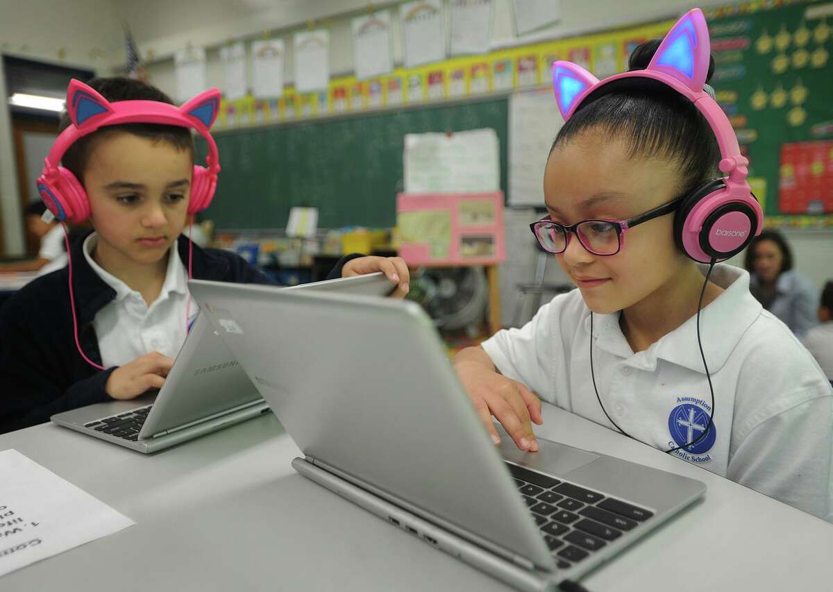 Assumption Catholic School students working with laptops in May 2018 in Fairfield, Conn. As Connecticut schools contemplate offering online instruction during the coronavirus emergency, Charter Communications and Comcast are offering two months of free Internet to households with students that do not have existing accounts.