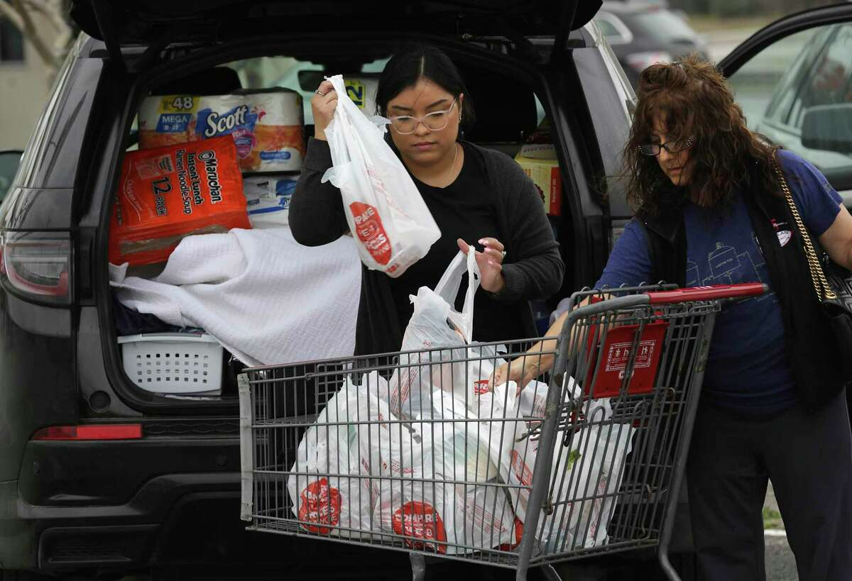 An H-E-B employee, left, helps a customer with her purchases. After the city announced Friday, March 13. 2020, that a person tested positive for coronavirus, area grocery stores, including one on Austin Highway, experienced a run on water, toilet paper and other items.