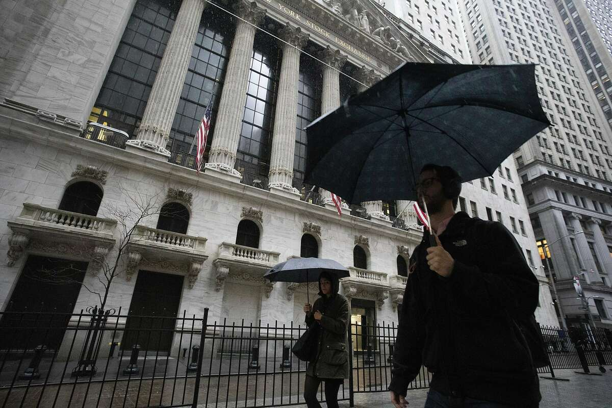 People walk in the rain as they pass the the New York Stock Exchange, Friday, March 13, 2020. European stocks rose Friday and Wall Street was set to gain on the open after turbulent trading in Asia and a day after the market's worst session in over three decades. (AP Photo/Mark Lennihan)