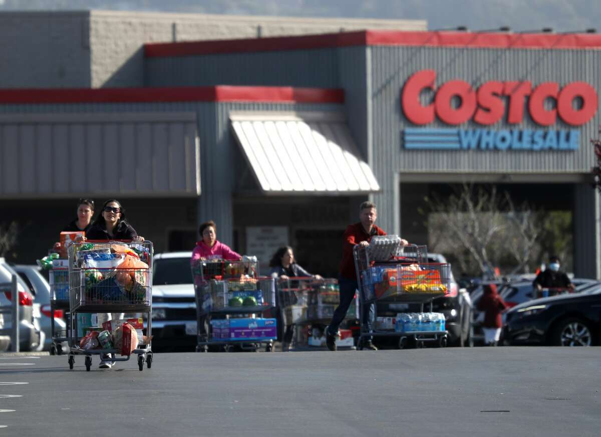 Costco customers push shopping carts through the parking lot of a Costco store on March 13, 2020 in Richmond. Some Americans are stocking up on food, toilet paper, water, and other items after the World Health Organization (WHO) declared Coronavirus (COVID-19) a pandemic.