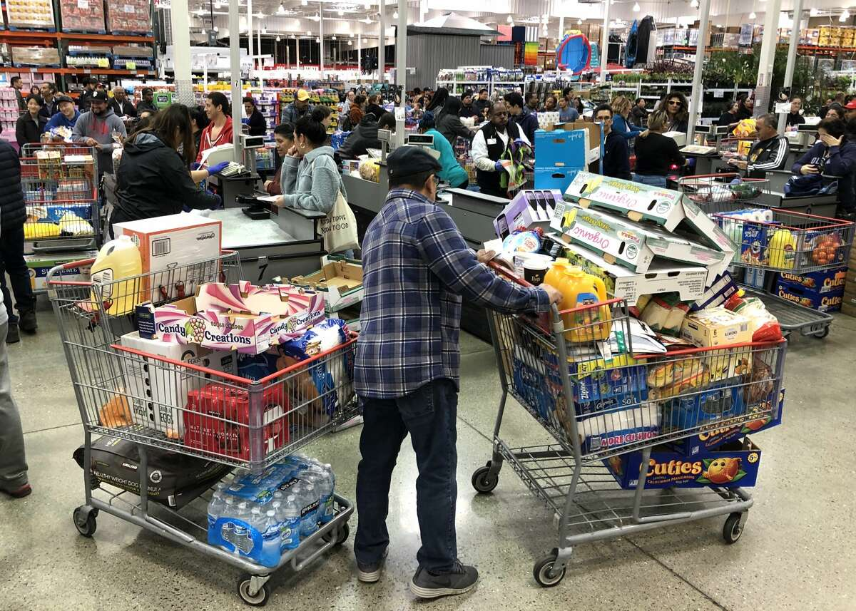 A Costco customer stands by his two shopping carts at a Costco store on March 13, 2020 in Richmond. Some Americans are stocking up on food, toilet paper, water and other items after the World Health Organization (WHO) declared Coronavirus (COVID-19) a pandemic.