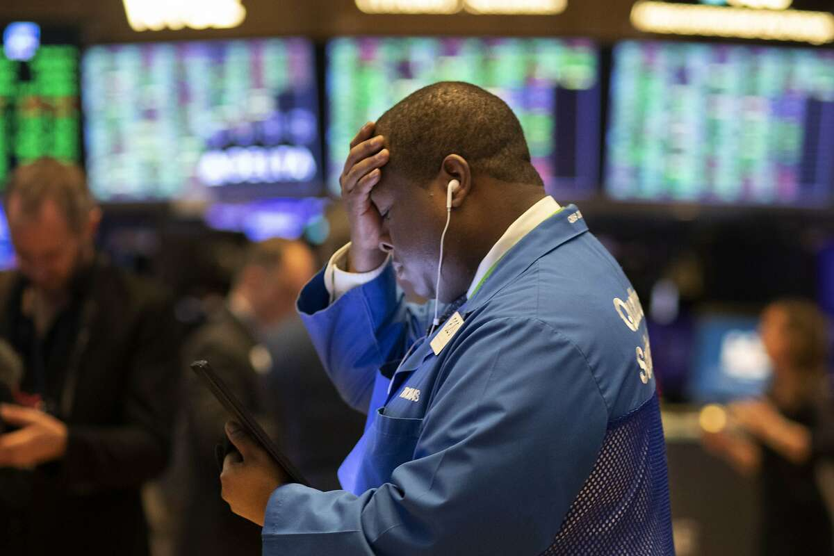 Stock trader Thomas Lee works at the New York Stock Exchange, Friday, March 13, 2020. Stocks are opening sharply higher on Wall Street a day after the worst drop since 1987. (AP Photo/Mark Lennihan)