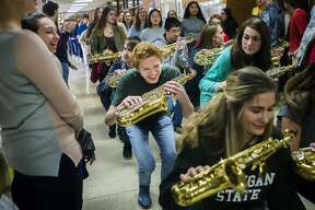 Dow High student TJ Newtonfield, center, crouches down as he dances through the hallway with the marching band as they perform during a pep rally Thursday, March 12, 2020 in support of Dow teams that were supposed to move forward in their prospective state tournaments. All MHSAA sporting events have been postponed as a preventative measure to curb the spread of COVID-19. (Katy Kildee/kkildee@mdn.net)