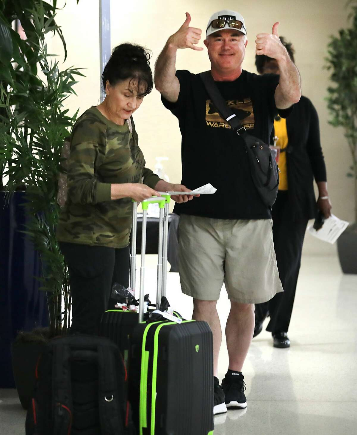 A man and a woman, both evacuees from the coronavirus-infected Diamond Princess cruise ship in Japan, give thumbs up after using hand sanitizer having just arrived at the San Antonio International Airport from Joint Base San Antonio Lackland where they were quarentined, on Tuesday, March 3, 2020.