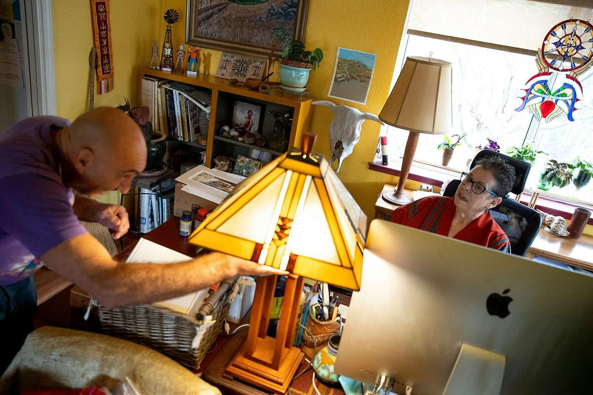 From left: David Stahlberg wipes down his home as Donnee Komisar uses her computer at home on Friday, March 13, 2020, in Cotati, Calif. They recently returned from Italy. Komisar became ill with what her doctor thinks is COVID-19.