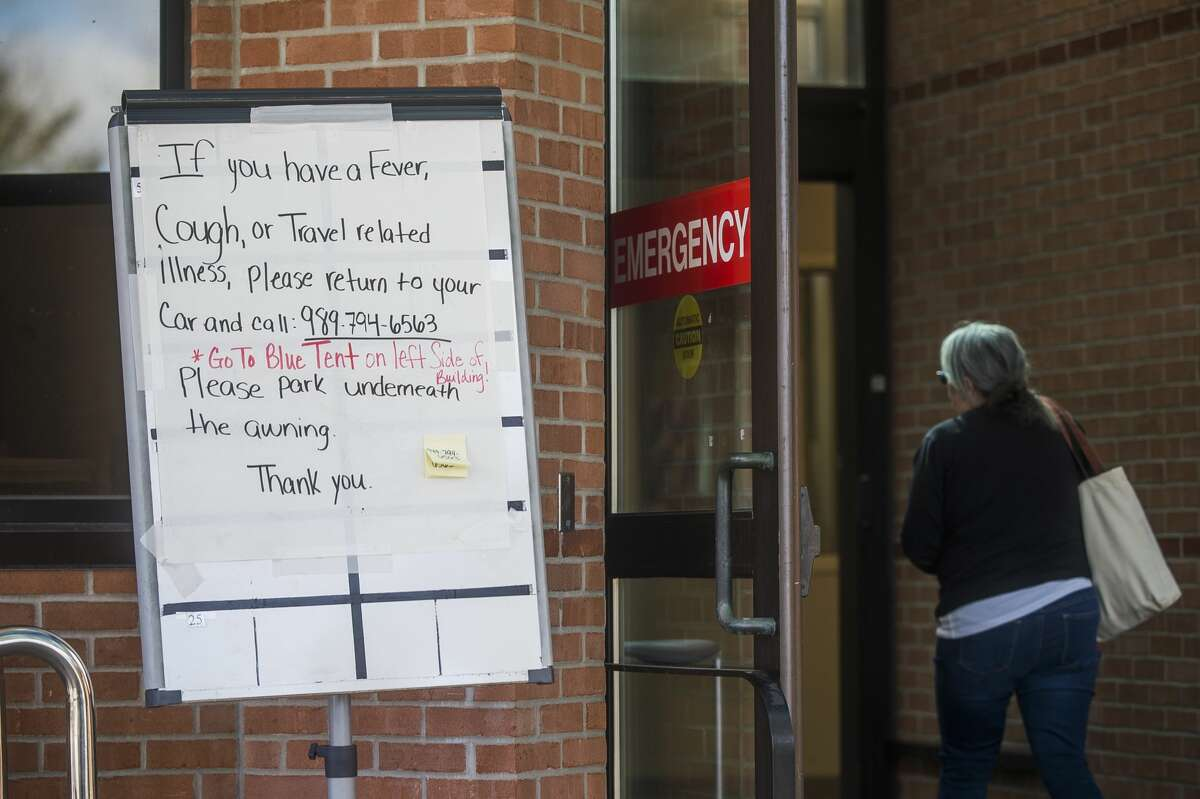 A sign instructs people what to do if they have a fever, cough or travel related illness, outside of the Emergency Department at MidMichigan Medical Center-Midland Friday, March 13, 2020. (Katy Kildee/kkildee@mdn.net)