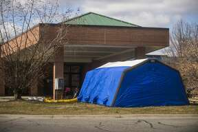 """A COVID-19 testing tent is set up outside of the Emergency Department atMidMichiganMedical Center-Midland Friday, March 13, 2020. """"These measures have been put in place to help distance those with a concern about COVID-19 exposure from the rest of our patient population and our staff, health care providers and volunteers,""""said Lydia Watson,M.D., senior vice president and chief medical officer,MidMichiganHealth. (KatyKildee/kkildee@mdn.net)"""