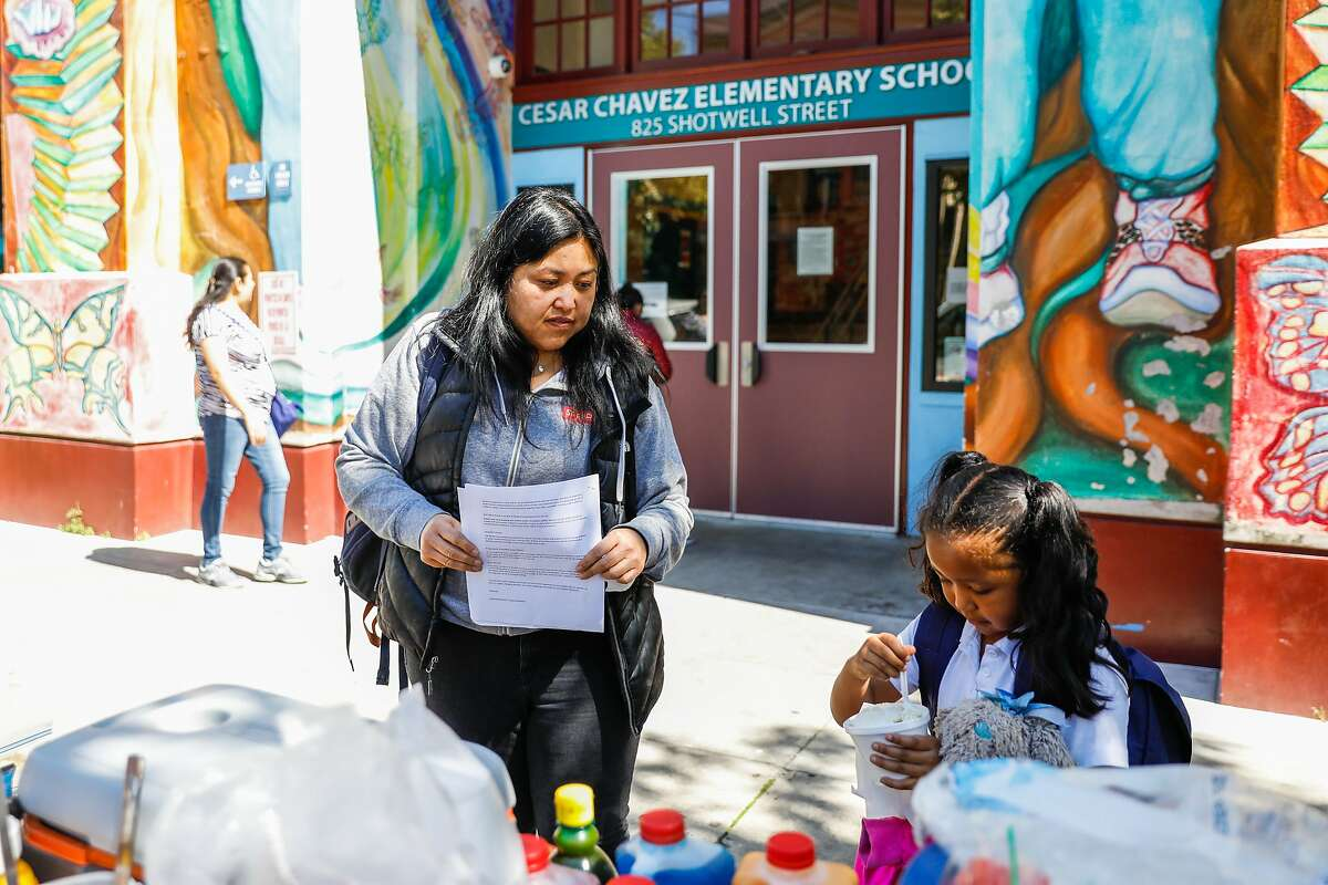 Maritess Villanueva (left) gets her daughter Bela Fuller, 6 a snack after getting picked up from Cesar Chavez Elementary School on Thursday, March 12, 2020 in San Francisco. The school board voted Tuesday to change the elementary school assignment process.