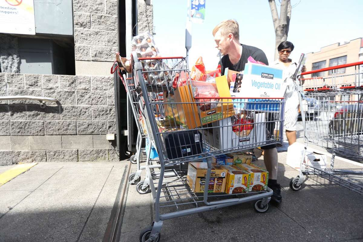 Shoppers leave Costco in San Francisco, Friday, March 13, 2020.