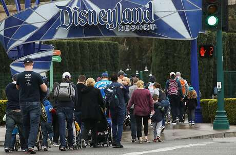 ANAHEIM, CALIFORNIA - MARCH 13: Disneyland visitors enter the famed amusement park on March 13, 2020, in Anaheim, California. Walt Disney Co. is shuttering Disneyland Park and Disney California Adventure tomorrow until the end of the month due to the spread of COVID-19. (Photo by Mario Tama/Getty Images)