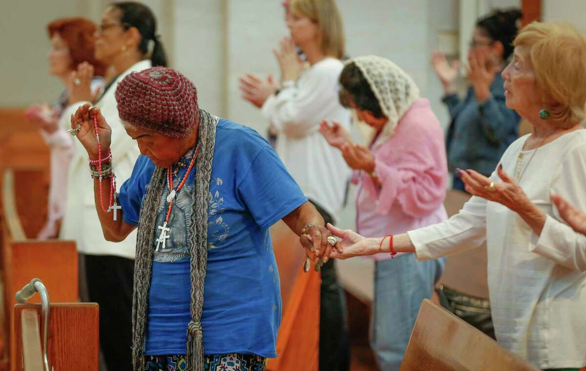 The faithful pray the Lord's Prayer during the midday Mass in the Co-Cathedral of the Sacred Heart Friday, March 13, 2020, in Houston.