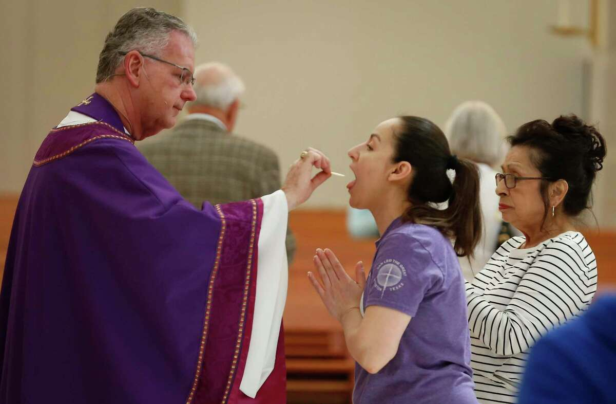 Fr. Lawrence W. Jozwiak gives the faithful the Eucharist, but not Precious Blood, due to the COVID-19 outbreak during the midday Mass in the Co-Cathedral of the Sacred Heart Friday, March 13, 2020, in Houston.