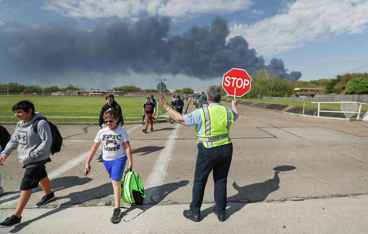 Deer Park PD crossing guard Adell Boren makes sure Deer Park Junior High School students are safe as they cross East 13th and Meadowlark streets as a chemical fire burns nearby March 19, 2019.