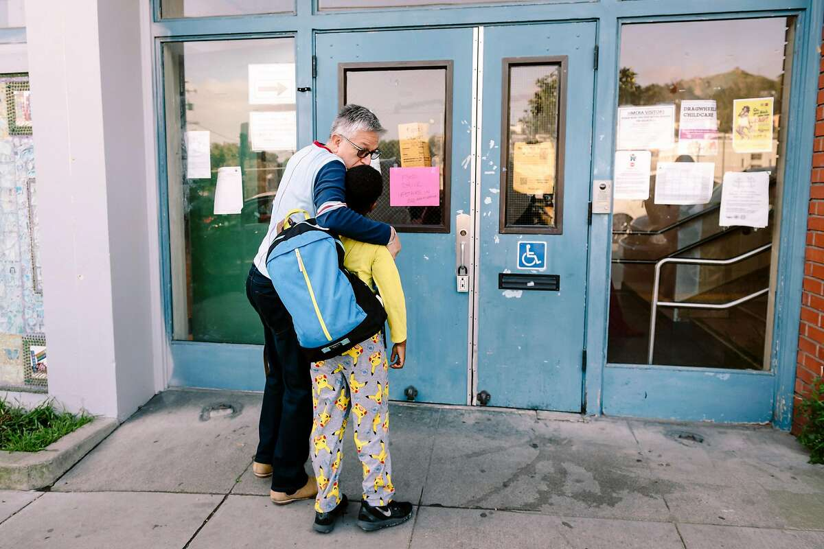 Willie Ramirez gives his son Akeem Ramirez, 8 years old, a kiss goodbye during morning drop-off at Harvey Milk Civil Rights Academy in San Francisco, California, US, on Friday, March 13, 2020.