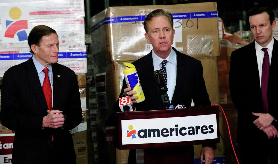 Gov. Ned Lamont and U.S. Senators Richard Blumenthal and Christopher Murphy visited Americares' headquarters and global distribution center at 88 Hamilton Ave., in Stamford, Conn., to receive an update on the health-focused relief and development organization's response to the COVID-19 pandemic on March 13, 2020. Lamont holds a container of cleaning wipes as he speaks with the media. Photo: Matthew Brown / Hearst Connecticut Media / Stamford Advocate