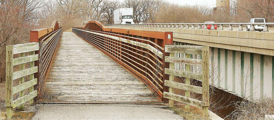 One of the many Madison County Transit funded trails in the area runs atop the Alton-Wood River industrial levee adjacent to Illinois 143, right, and Illinois 3. A wooden deck bridge, left, brings the trail across Wood River Creek.