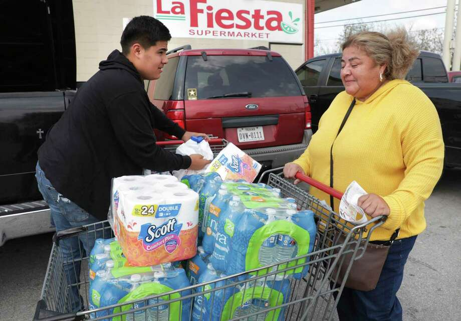 Anna Saenz, right, gets help from son Gabriel Thomas while loading groceries including water and toilet paper Friday, March 13, 2020. Photo: Bob Owen /Staff Photographer / ©2020 San Antonio Express-News